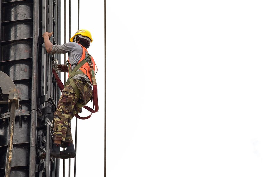 man climbing tower using PPE
